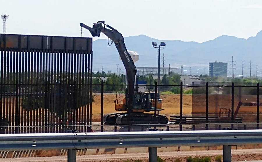 A crane operator works on a panel of 30-foot steel bollard wall in the Ysleta area of El Paso this week. A smaller, older section of border fencing can be seen to the side. (Border Report Photo/Julian Resendiz)