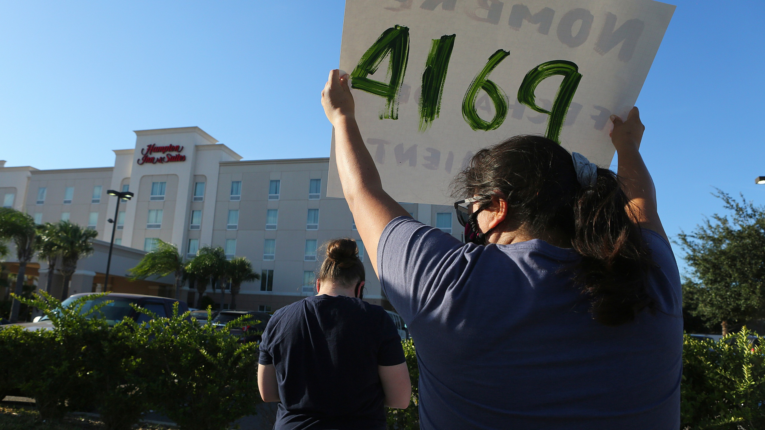 FILE - In this July 23, 2020, file photo, protesters wave signs in front of the Hampton Inn hotel in McAllen, Texas. The Trump administration has sharply increased its use of hotels to detain immigrant children as young as 1 before expelling them from the United States during the coronavirus pandemic despite facing outcry from lawmakers and human-rights advocates. (Joel Martinez/The Monitor via AP, File)