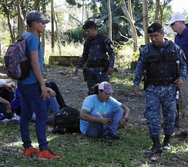 FILE - In this Jan. 15, 2020 file photo, an agent from U.S. Immigration and Customs Enforcement, far right, accompanies Guatemalan police at the checkpoint where they detain Honduran migrants before deporting them, in Morales, Guatemala. In a report released Tuesday, Oct. 13, 2020, by the Democratic staff of a U.S. Senate committee says U.S. immigration agents assigned to Guatemala to advise local authorities violated terms of their funding by helping officials deport Hondurans traveling in a migrant caravan early this year. (AP Photo/Moises Castillo, File)