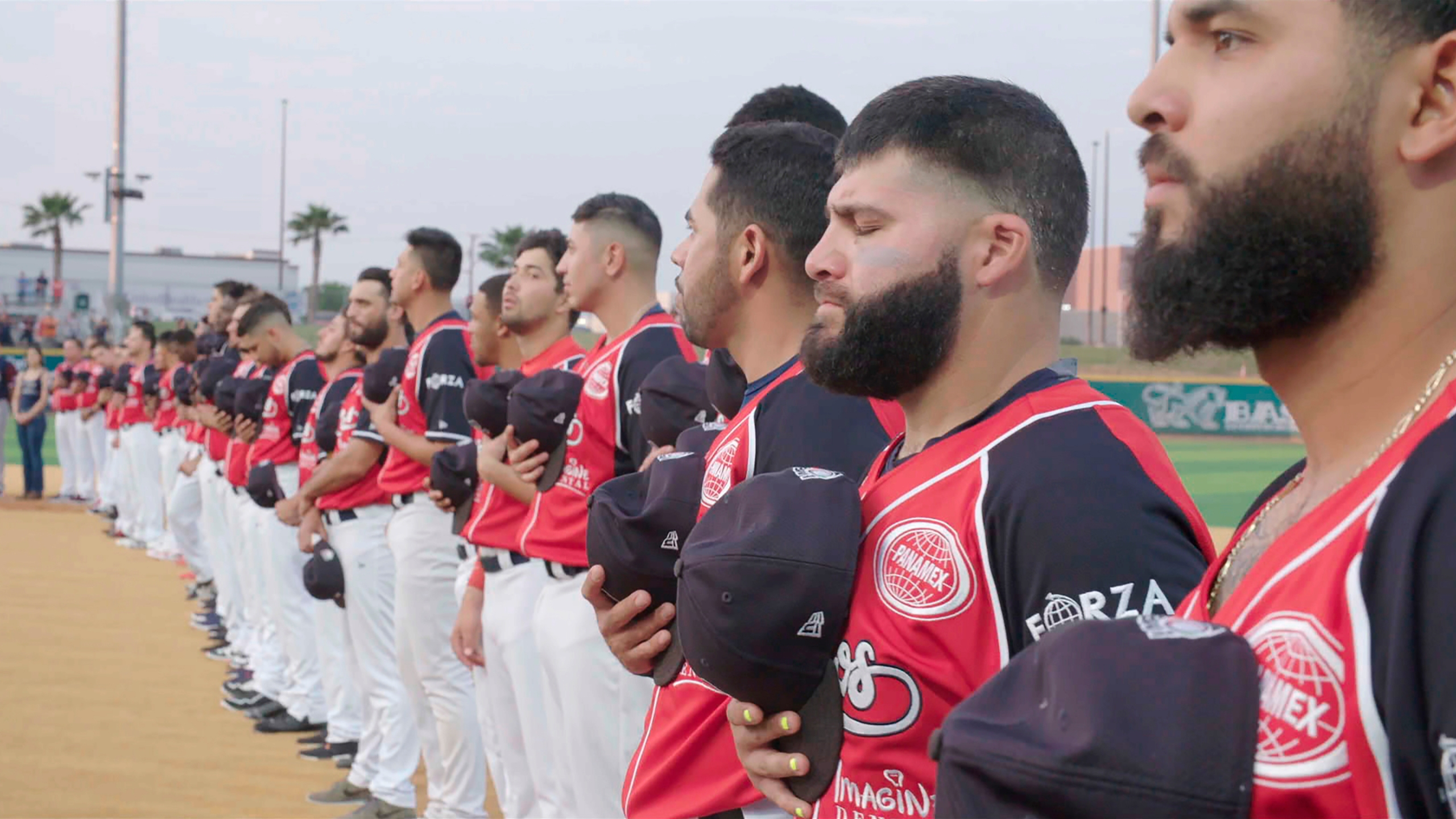 "Members of the Tecolotes de los Dos Laredo, a binational professional baseball team with home stadiums in Nuevo Laredo, Mexico, and Laredo, Texas, stand for the U.S. National Anthem before a game in 2019 in Laredo, Texas in a scene from ""Bad Hombres."" The Showtime documentary follows this AAA Mexican League baseball team that plays on both sides of the U.S.-Mexico border amid the tension around migration, divisive politics, and environmental concerns. (Showtime via AP)"