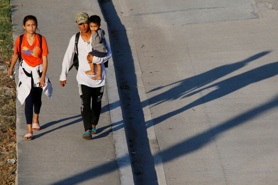 Migrants who aim to reach the U.S. leave San Pedro Sula, Honduras by foot early Tuesday, March 30, 2021. (AP Photo/Delmer Martinez)