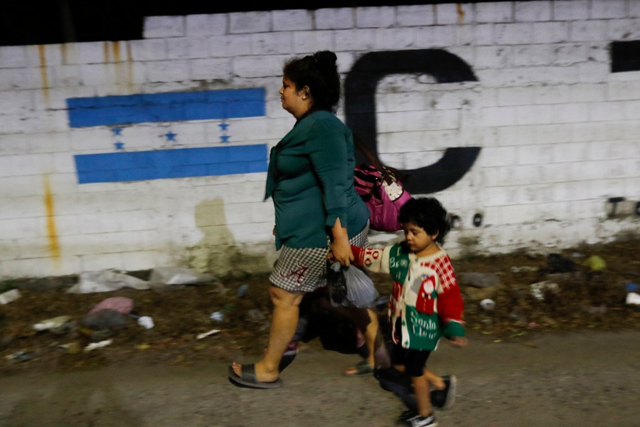 A woman who aims to reach the U.S. walks along a highway with two children as they leave San Pedro Sula, Honduras with a group of migrants before dawn Tuesday, March 30, 2021. (AP Photo/Delmer Martinez)