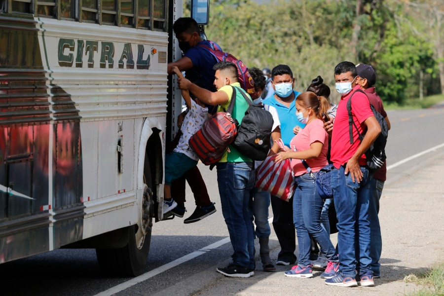 Honduran migrants board a bus to return home after local authorities prevented them from moving across the border for lack of papers, in Corinto, Honduras, Tuesday, March 30, 2021. Hundreds of Honduran migrants started to move towards the Guatemalan border with the hope of making it to the U.S., even as local authorities worked to prevent them from doing so. (AP Photo/Delmer Martinez)