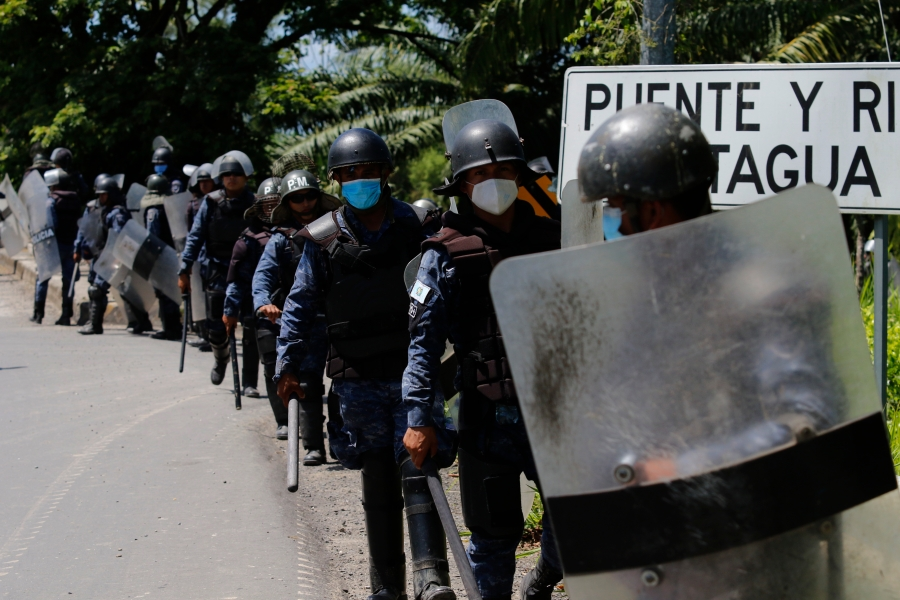 Guatemalan soldiers in riot gear guard the integrated border crossing point of Corinto on the border with Honduras as groups of Honduran migrants are expected to arrive, in Guatemala, Tuesday, March 30, 2021. Hundreds of Honduran migrants started to move towards the Guatemalan border with the hope of making it to the U.S., even as local authorities worked to prevent them from doing so. (AP Photo/Delmer Martinez)