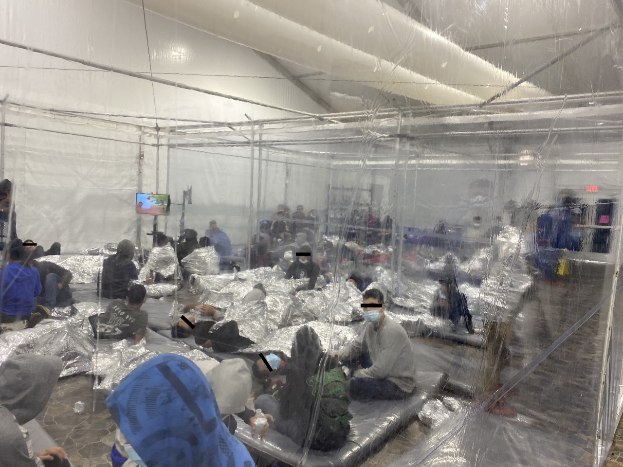 Migrants sleep under mylar blankets inside the U.S. Customs and Border Protection processing facility in Donna, Texas. (Courtesy photo by U.S. Rep. Henry Cuellar)