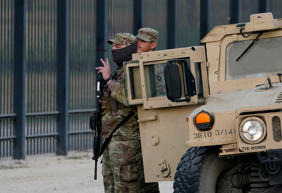 National Guardsmen stands watch over a fence near the International bridge where thousands of Haitian migrants have created a makeshift camp, Saturday, Sept. 18, 2021, in Del Rio, Texas. The Biden administration plans the widescale expulsion of Haitian migrants from a small Texas border city by putting them on on flights to Haiti starting Sunday, an official said Friday, representing a swift and dramatic response to thousands who suddenly crossed the border from Mexico and gathered under and around a bridge.(AP Photo/Eric Gay)