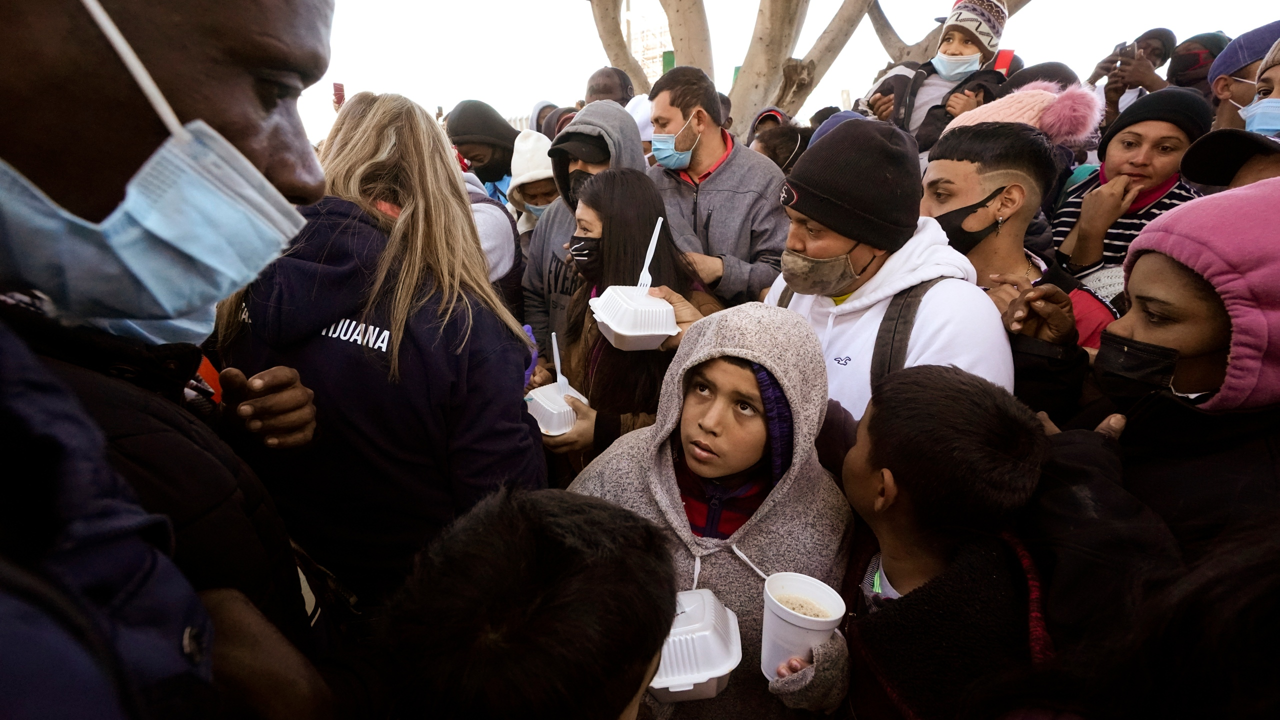 """FILE — In this Feb. 19, 2021 file photo asylum seekers receive food as they wait for news of policy changes at the border, in Tijuana, Mexico. The Biden administration outlined a plan to reinstate a border policy that made asylum-seekers wait in Mexico for hearings in U.S. immigration court. Details were disclosed in a court filing after a federal judge in Texas ordered that the policy by resumed """"in good faith,"""" having started under President Donald Trump and sending about 70,000 people back to Mexico until Biden abruptly ended because he felt it was inhumane. (AP Photo/Gregory Bull, File)"""